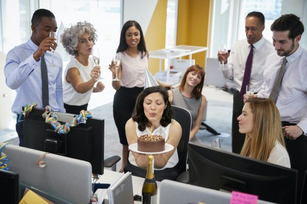 Colleagues gathered at woman's desk to celebrate a birthday and listen to Matthew McConaughey impression birthday wishes