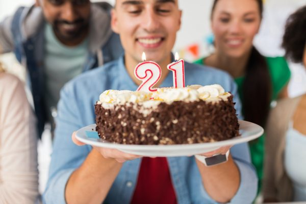 man with cake and friends at birthday party